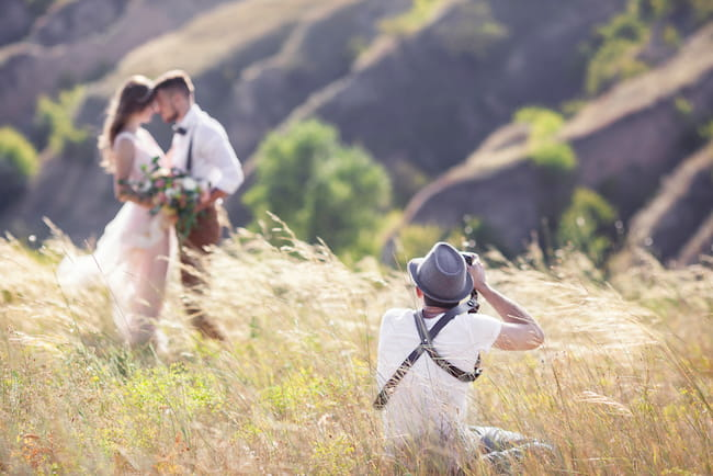 Wedding Photographer taking pictures of couple in field