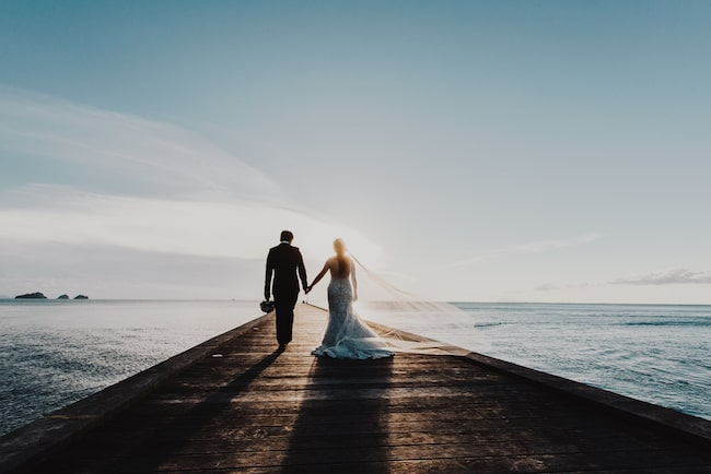 Wedding couple walking down a pier